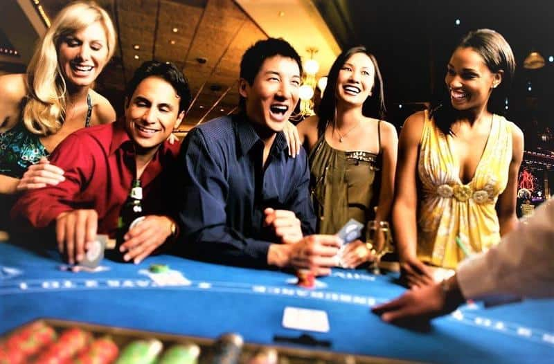 a happy group of people around a casino table