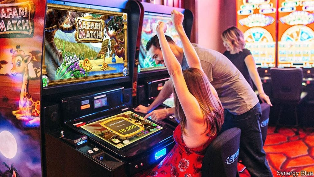 a man and a woman cheering in front of a slot machine
