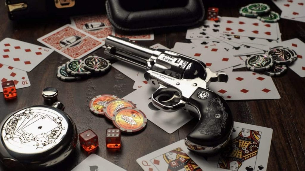a gun next to casino chips and cards on a wooden table