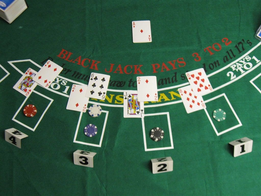 green blackjack table with cards on it