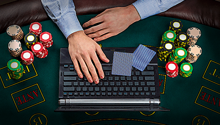 a man palying a casini game on his laptop with cards and poker chips next to him