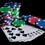 poker chips and casino cards on a black table