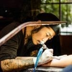 a tattoo artist tattooing a person's arm