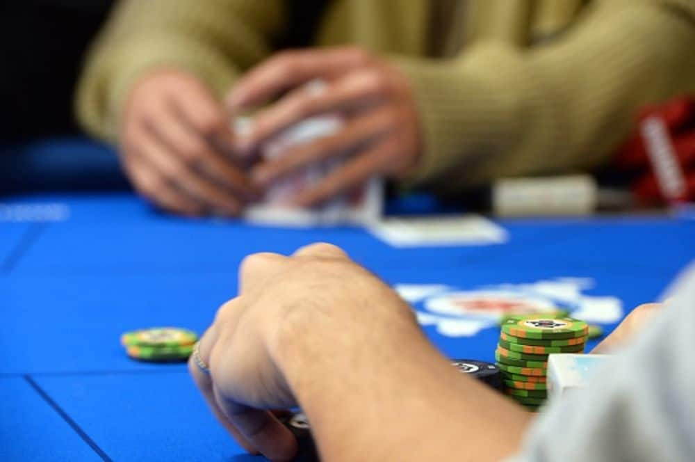 two people sitting on a poker table