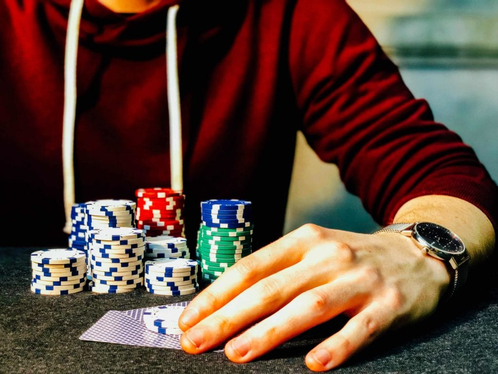 a male's hand with poker chips and poker cards near it