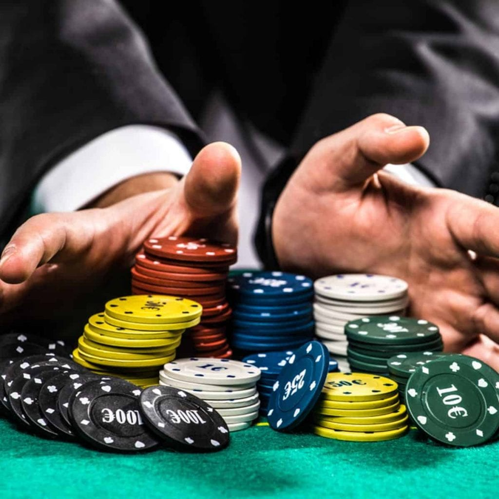 a man holding  poker chips in front of him