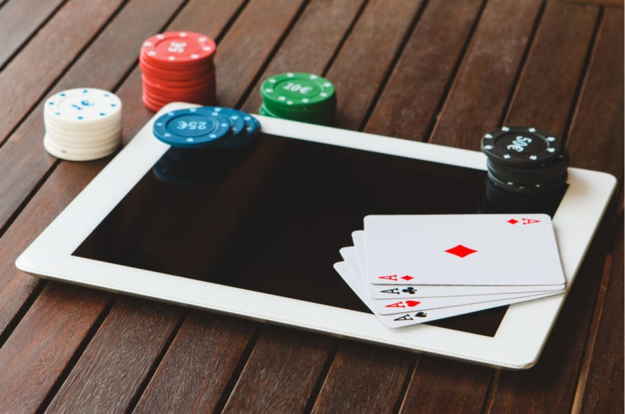 a tablet with cards and poker chips placed on it
