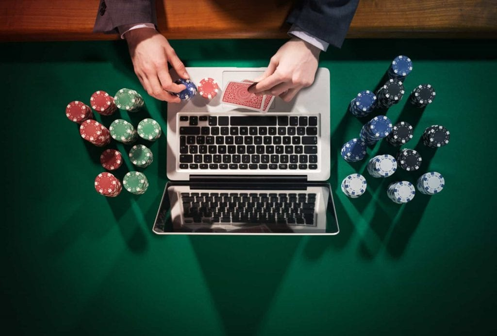 a man playing on his laptop with poker chips by his side