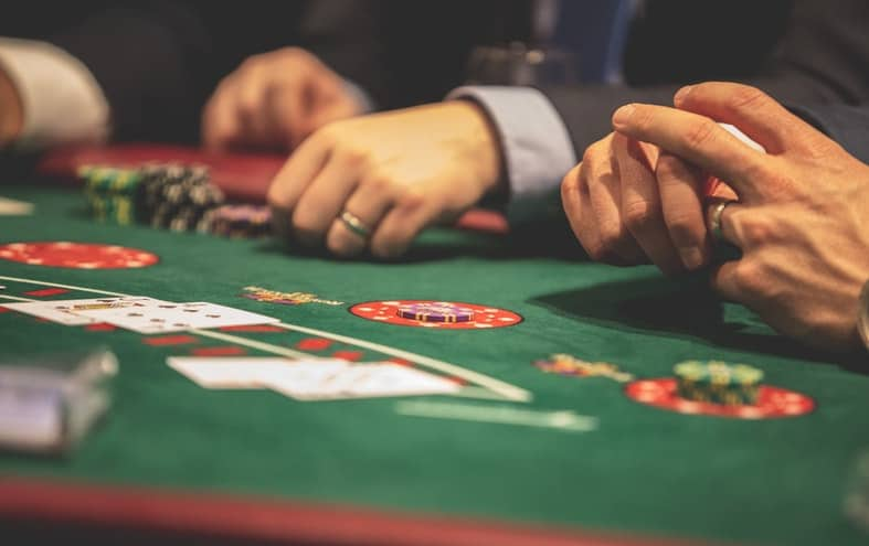 an image of people holding poker chips on a casino table with their hands showing