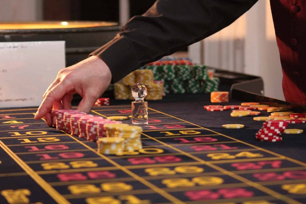 a man holding poker chips on a casino table