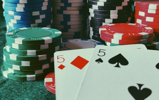 cards and poker chips laying on a green casino table