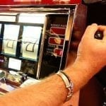 a hand pulling the handle of a slot machine